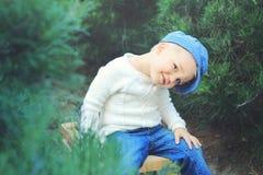 Niño pequeño lindo en árboles de pino Fotografía de archivo