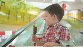 Niño pequeño lindo en carro de la compra con helado sabroso durante compras de la familia en hipermercado almacen de video