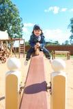 Niño pequeño lindo en el oscilación Foto de archivo