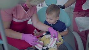 Niño pequeño lindo en la oficina del dentista El doctor que enseña al pequeño paciente a cepillar los dientes usando la mofa del  almacen de metraje de vídeo