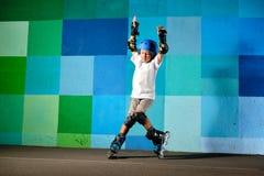 Niño pequeño lindo en los pcteres de ruedas que corren contra la pared azul de la pintada imagen de archivo