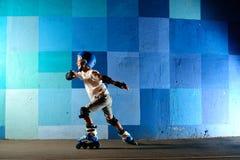 Niño pequeño lindo en los pcteres de ruedas que corren contra la pared azul de la pintada Fotografía de archivo libre de regalías