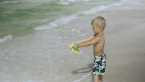 Niño pequeño lindo en un bañador que juega con el cubo en la playa 4k almacen de video