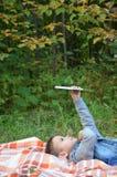Niño pequeño lindo en un parque del otoño en una manta Lee juegos una tableta digital inalámbrico electrónico Fotos de archivo