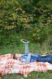Niño pequeño lindo en un parque del otoño en una manta Lee juegos una tableta digital inalámbrico electrónico Foto de archivo