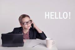 Niño pequeño lindo en un traje que habla en el teléfono imagenes de archivo