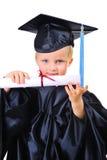 Niño pequeño lindo en vestido de la graduación Fotos de archivo