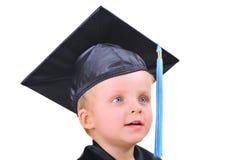 Niño pequeño lindo en vestido de la graduación Fotos de archivo libres de regalías