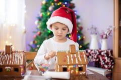 Niño pequeño lindo, haciendo la casa de las galletas del pan de jengibre para la Navidad Imagen de archivo