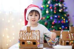 Niño pequeño lindo, haciendo la casa de las galletas del pan de jengibre para la Navidad Imagen de archivo libre de regalías