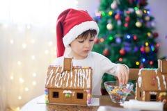 Niño pequeño lindo, haciendo la casa de las galletas del pan de jengibre para la Navidad Foto de archivo libre de regalías