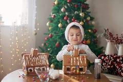 Niño pequeño lindo, haciendo la casa de las galletas del pan de jengibre para la Navidad Imágenes de archivo libres de regalías