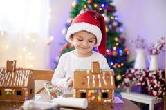 Niño pequeño lindo, haciendo la casa de las galletas del pan de jengibre para la Navidad Fotos de archivo