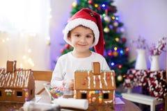 Niño pequeño lindo, haciendo la casa de las galletas del pan de jengibre para la Navidad Imagenes de archivo