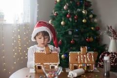 Niño pequeño lindo, haciendo la casa de las galletas del pan de jengibre para la Navidad Foto de archivo