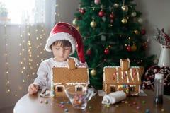 Niño pequeño lindo, haciendo la casa de las galletas del pan de jengibre para la Navidad Fotos de archivo libres de regalías
