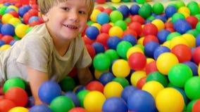 Niño pequeño lindo, niño, jugando en bolas coloridas en patio de los niños, dentro metrajes