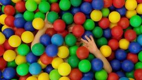 Niño pequeño lindo, niño, jugando en bolas coloridas en patio de los niños, visión desde el aboeve metrajes