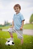 Niño pequeño lindo, jugando a fútbol fotos de archivo