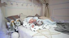 Niño pequeño lindo, pequeños sueños del niño, bebé que miente en la cama en los resbaladores y casquillo, muchacho lindo del sueñ almacen de video
