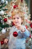 Niño pequeño lindo que adorna el árbol de navidad Foto de archivo libre de regalías