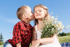 Niño pequeño lindo que besa a la muchacha Imagen de archivo