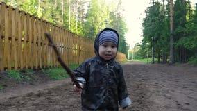 Niño pequeño lindo que camina en el camino rural del país en el parque, divirtiéndose y jugando con el palillo almacen de metraje de vídeo