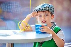 Niño pequeño lindo que come el helado en el café interior imagenes de archivo