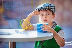 Niño pequeño lindo que come el helado en el café interior Foto de archivo