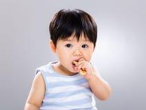 Niño pequeño lindo que come la galleta Foto de archivo libre de regalías