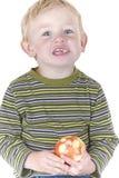 Niño pequeño lindo que come la manzana foto de archivo libre de regalías