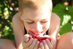 Niño pequeño lindo que come una fresa Foto de archivo libre de regalías