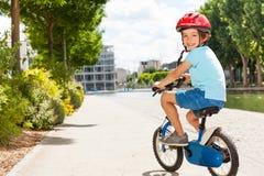 Niño pequeño lindo que completa un ciclo en el parque de la ciudad en verano Imagen de archivo