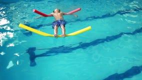Niño pequeño lindo que flota en la piscina almacen de video