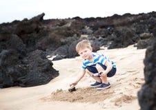 Niño pequeño lindo que juega con las rocas de la lava Imagen de archivo libre de regalías