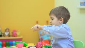 Niño pequeño lindo que juega con las verduras plásticas almacen de metraje de vídeo