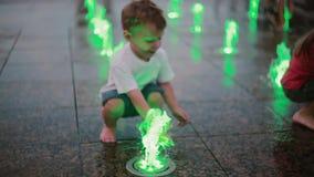 Niño pequeño lindo que juega con los chorros de agua coloreados en la fuente en el día de verano caliente, corriendo al grupo de  almacen de video