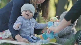 Niño pequeño lindo que juega con los juguetes en una sobrecama en parque almacen de video