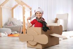 Niño pequeño lindo que juega con los prismáticos y el aeroplano de la cartulina imagen de archivo libre de regalías