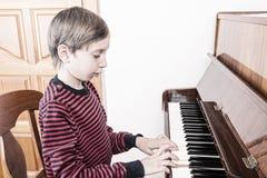 Niño pequeño lindo que juega el piano con la expresión divertida Fotografía de archivo