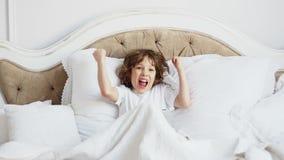 Niño pequeño lindo que juega en el suyo a juegos digitales de tableta de la cama almacen de metraje de vídeo