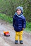 Niño pequeño lindo que juega en la primavera afuera El niño de dos años lleva un camión en una secuencia Sonrisa, emociones posit fotos de archivo libres de regalías