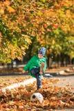 Niño pequeño lindo que juega a fútbol en el parque del otoño foto de archivo libre de regalías