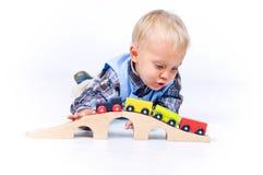Niño pequeño lindo que juega los trenes Foto de archivo
