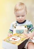 Niño pequeño lindo que lee un libro Imagen de archivo libre de regalías