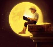 Niño pequeño lindo que lee un libro en la luz de luna Imagenes de archivo