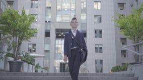 Niño pequeño lindo que lleva un traje de negocios con el caso que camina en la ciudad Niño como adulto almacen de metraje de vídeo