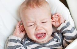 Niño pequeño lindo que llora sosteniéndose el oído Foto de archivo libre de regalías
