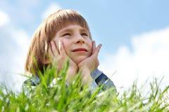 Niño pequeño lindo que pone en hierba verde sobre natur de la primavera del cielo azul imagen de archivo libre de regalías