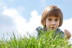 Niño pequeño lindo que pone en la naturaleza de la primavera de la hierba verde al aire libre fotos de archivo